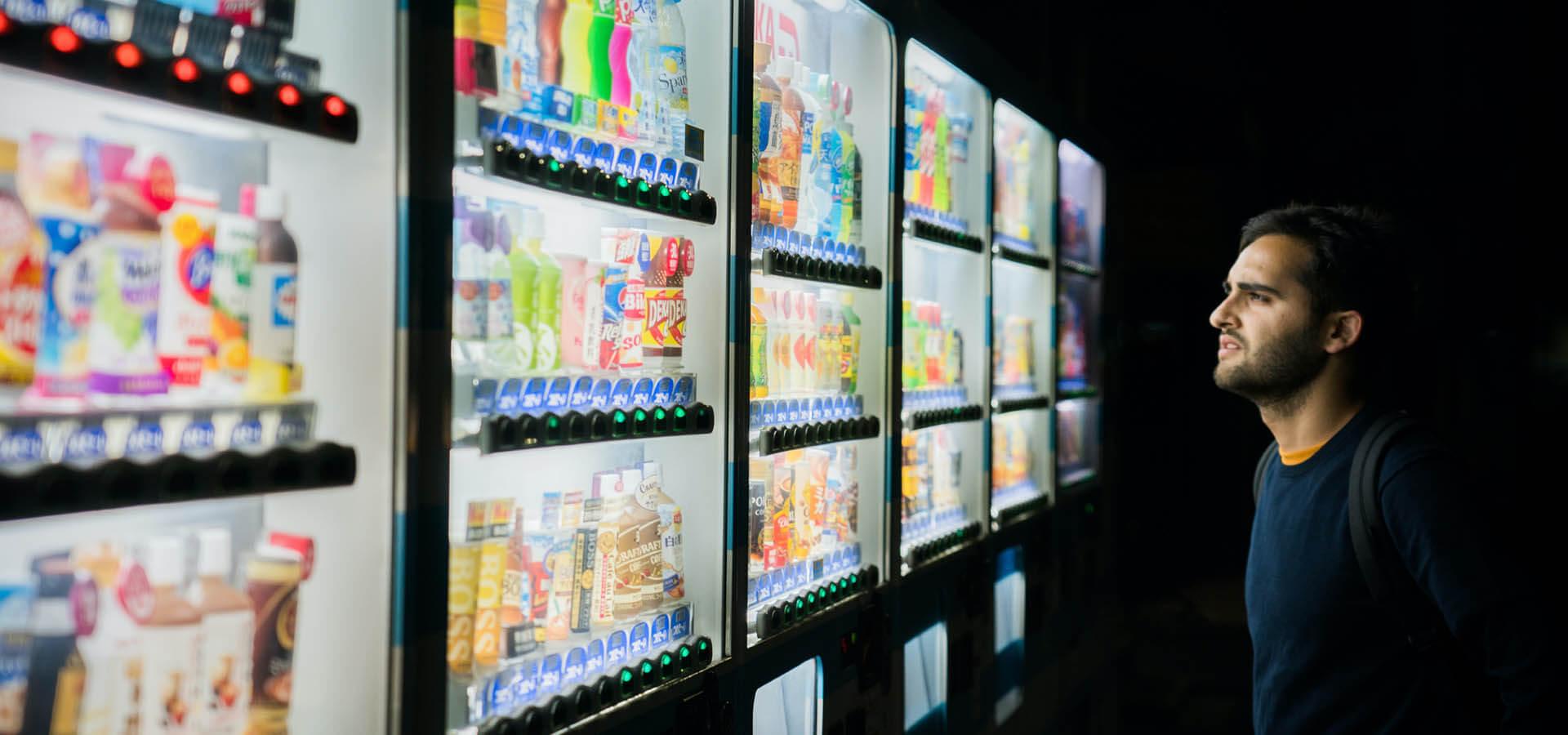 Man looking at drinks in vending machines